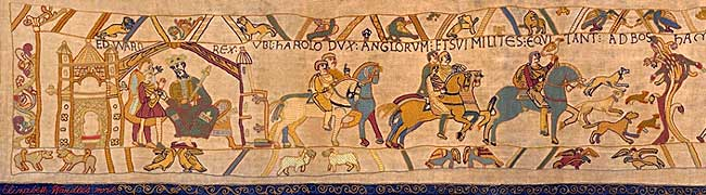 Beige Tapestry that illustrates horsemen, horses, dogs and sheep and has a blue border as well.