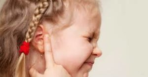 Little girl with pig tails, clutching her ear and shutting her eyes tight