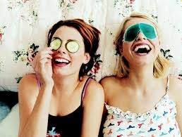 two girls laughing lying down with eye masks on