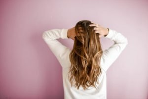 pink background, white sweater girl back showing with long hair
