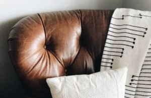 Leather Cleaning- Brown Leather Couch close up with white pillow and black/white throw