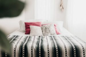Bed with black and white duvet and assorted throw pillows
