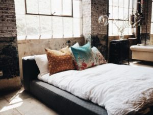 White mattress on bed with throw pillows