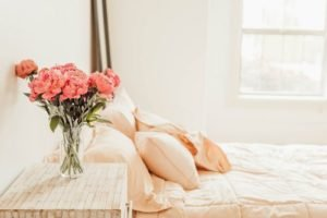 Peach toned bedroom with pink flowers on the bedside table - Who Who Carpet Cleaning Blog