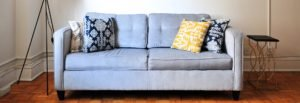 Upholstery Cleaning Brisbane- Grey Two seater couch with yellow, blue and grey pillow - Who Who Carpet Cleaning and Pest Management