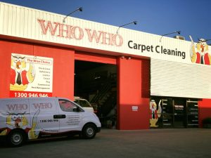 Red building with who who carpet cleaning owl logo and van parked out front