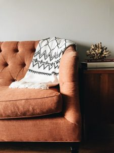 Brown upholstery couch with Aztec print throw - who who upholstery cleaning brisbane